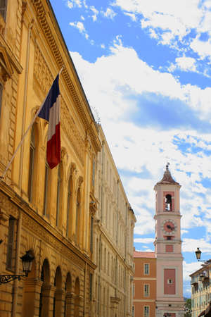clocktower: building with flag and church clocktower  in Nice, France Stock Photo