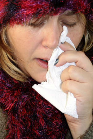 drippy: sick woman with a flu holding tissue Stock Photo