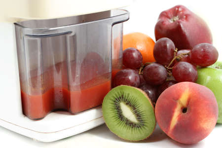 juicer: variety of fruit and freshly made  juice  in juicer