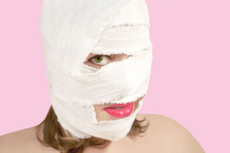 woman with bandages on the face after plastic surgery