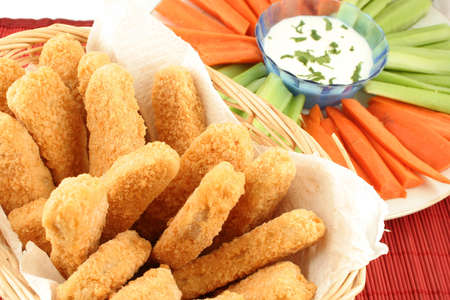 suppertime: basket of crispy chicken fingers with platter of vegetables and dip Stock Photo