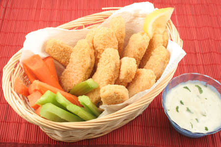 chicken fingers: basket of crispy chicken fingers with platter of vegetables and dip Stock Photo