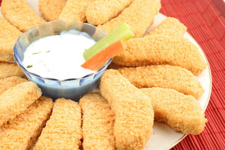 suppertime: plate of crispy chicken fingers with  vegetables and dip Stock Photo