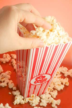 popped: grabbing freshly popped popcorn from striped bucket