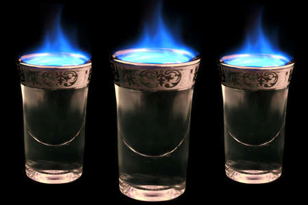 potent: shot glasses with alcohol on fire..... (drink up!!  :) Stock Photo