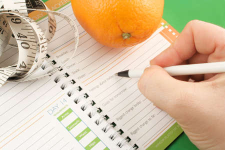 writing in a diet and nutrition journal with orange and tape measure to the side Stock Photo
