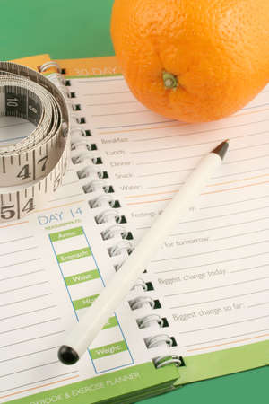 entries: writing in a diet and nutrition journal with orange to the side Stock Photo