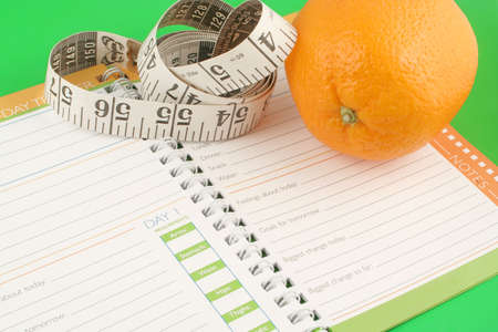 entries: a measuring tape, diet and nutrition journal and an orange