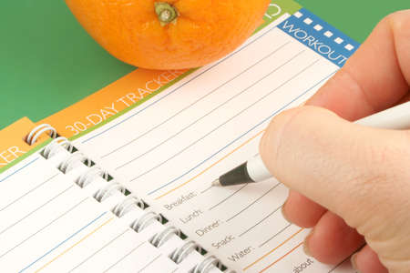 writing in a diet and nutrition journal with orange to the side photo
