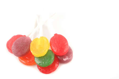 various rainbow colored  hard lollipop candy on white background
