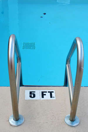 depth measurement: pool steel rails at the five foot deep end