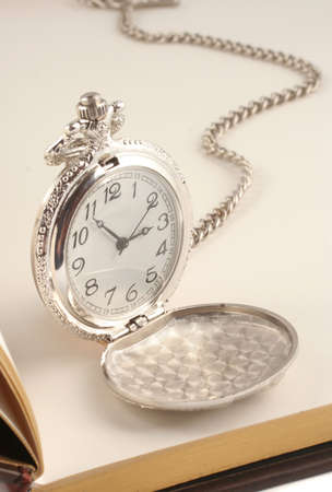 heirlooms: antique silver  pocket watch on top of blank book