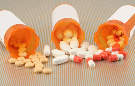 pills bottle: three different kinds of pills spilling out of cannisters Stock Photo