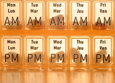 pharmaceutic: different kinds of pills in slots of  daily reminder cannister Stock Photo