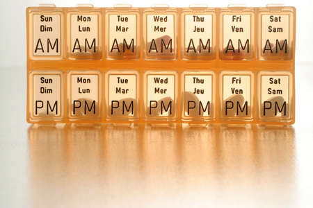 treating: different kinds of pills in slots of  daily reminder cannister Stock Photo