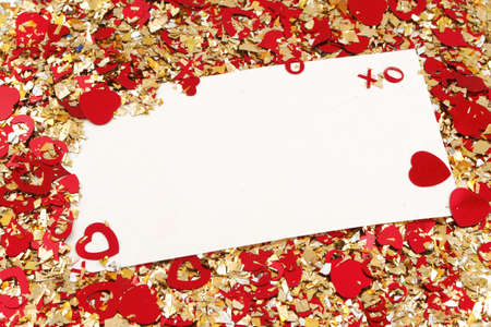 blank card on valentine confetti make of hearts and gold glitter
