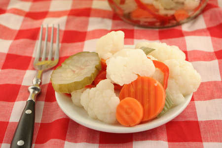 variety of pickled vegetables and pickle jar in background