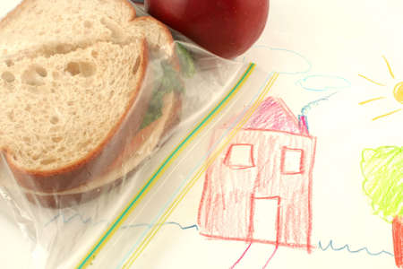bagged: whole wheat sandwich and apple (a healthy lunch) on top of child drawing in school Stock Photo