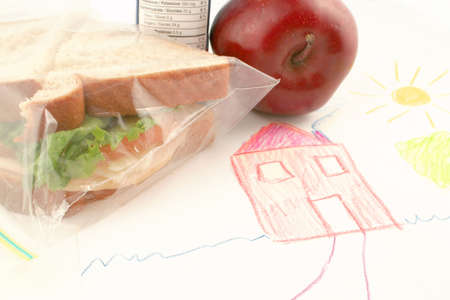 lunchtime: whole wheat sandwich, apple and juice (a healthy lunch) on top of child drawing in school