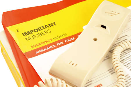 home telephone on top of phone directories and emergency numbers photo