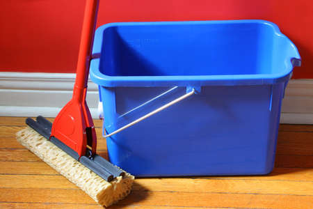 mop and blue bucket on hardwood floors with red wall in background