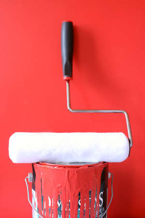 home decorating: paint roller on top of  red paint can for home decorating