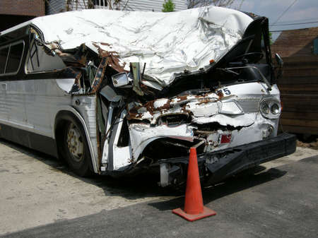 Smashed up bus in scrap yard after being totalled from an accident                       photo