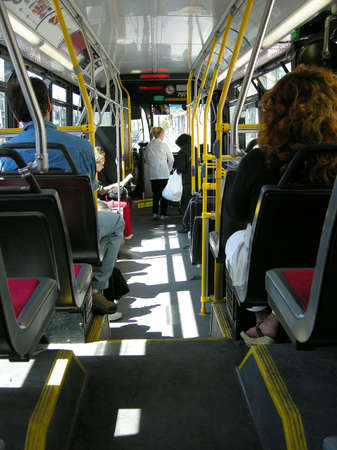 motorcoach: passengers getting off and on a city transit transportation bus
