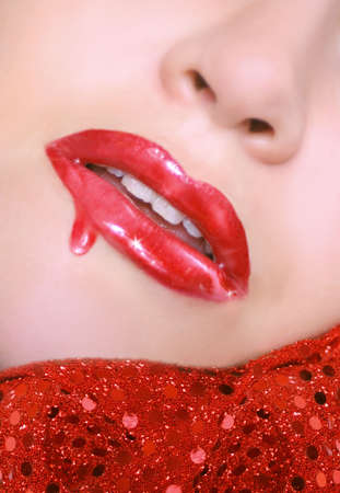 sexy red lips with dripping  lip gloss and chin resting on sequins photo