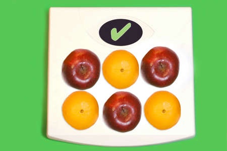 conceptual image of healthy food like fruit on scale with checkmark stating a healthy choice in diet