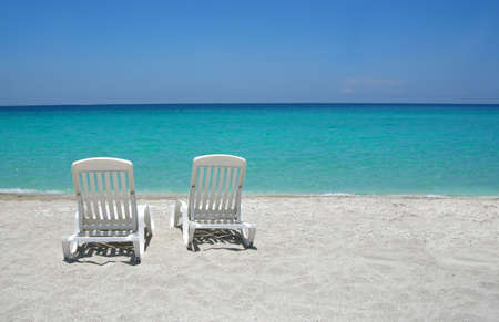 loungers: Empty tropical beach chairs on sand at shoreline in the Caribbean