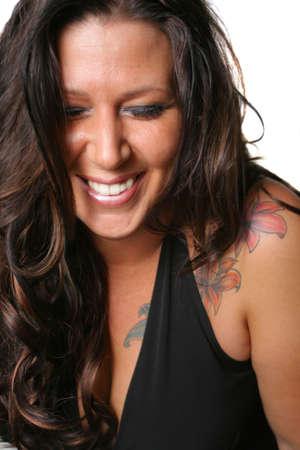 tattoed: Tatuada morena mujer sonriendo con los ojos cerrados en un fondo blanco  Foto de archivo