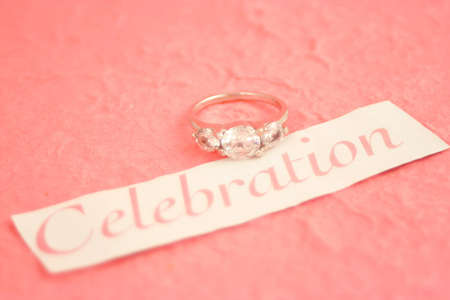 sparkling engagement ring on the word celebration and pink background