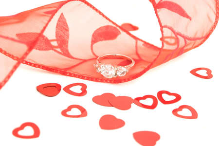 sparkling engagement ring on red ribbon surrounded by confetti hearts photo