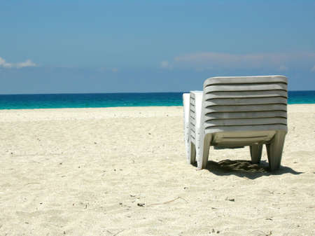Stacked up beach loungers on a tropical beach photo