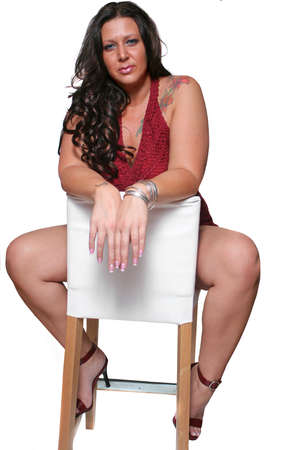 tattooed brunette full figured woman  relaxing with white backed stool