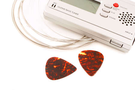 a guitar and bass portable string tuner, strings and guitar picks