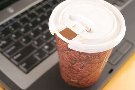 a cup of coffee to go on top of laptop Stok Fotoğraf