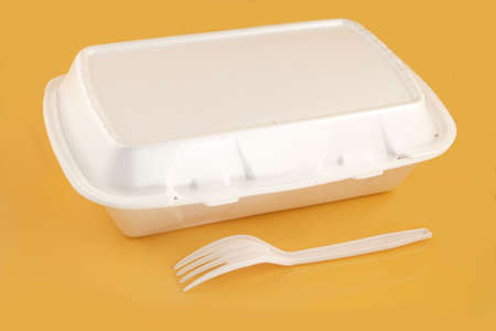 styrofoam take-out food container and plastic fork on a yellow background Stock Photo