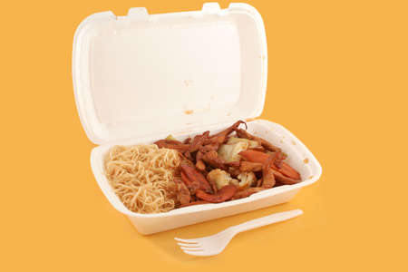 styrofoam take-out  container with Chinese food on a yellow background Stock Photo