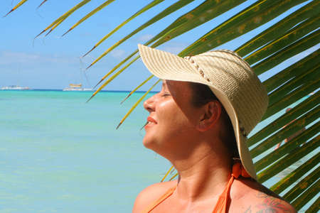 soaks: voluptuous woman soaks up the sun with palm backdrop on a tropical beach  Stock Photo