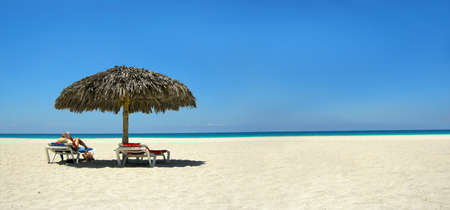 loungers: woman relaxing on a lounger reading a book at a tropical beach panorama
