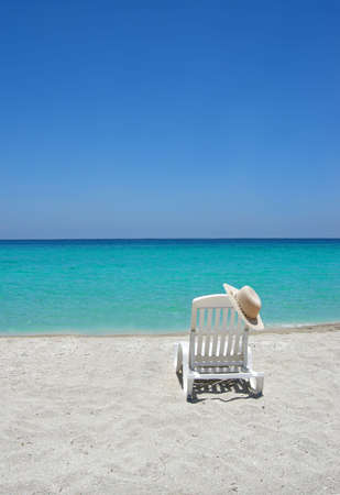shorelines: Empty tropical beach chair with hat  at shoreline in the Caribbean