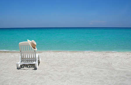 serenity: Empty tropical beach chairs on sand at shoreline in the Caribbean