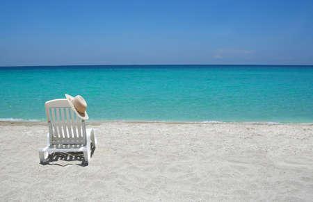 Lege tropisch strand stoelen op zand op kustlijn in het Caribisch gebied