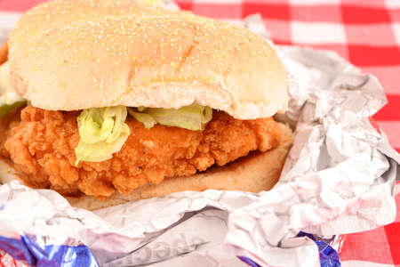 fast food crispy chicken burger still in wrapper with checkered red background