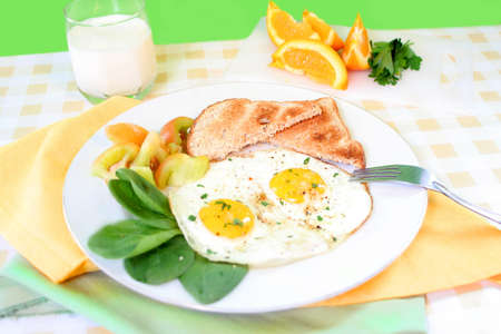 two sunny side up eggs on plate with fresh vegetables whole wheat toast and sliced orange in the background Stock Photo