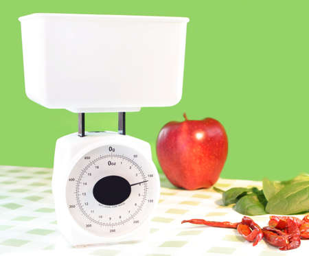 white food scale stating that something inside weighs 4 grams, apple, spinach and jalapeno peppers are on table beside it Stock Photo - 2731706