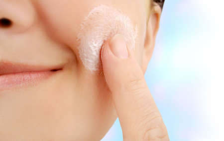 caucasian smiling woman applies moisturizer onto face Stock Photo - 2823677
