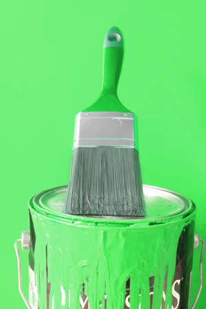 hues:  paintbrush on top of green  paint can for home decorating